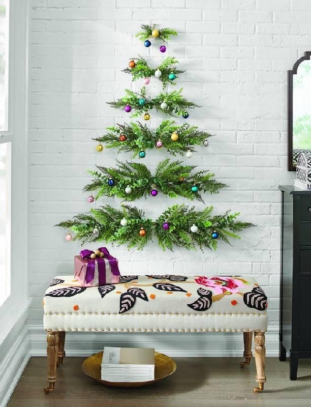 Arbre de Noël sur le mur avec des branches et des boules