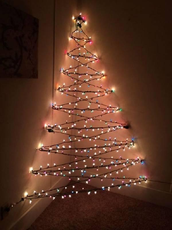 Des lumières colorées forment l'arbre de Noël dans le coin du mur